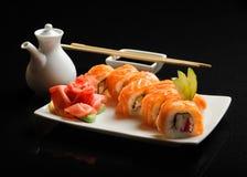 Sushi und Rollen auf einer quadratischen Platte mit Wasabi, Sojasoße und Essstäbchen auf einem schwarzen Hintergrund Stockbild