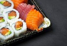 Sushi und Sashimi rollt auf einem schwarzen Stein-slatter Frisches Sushi gemacht, mit Lachsen, Garnelen, Wasabi und Ingwer einzus Stockfoto