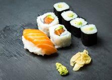 Sushi und Sashimi rollt auf einem schwarzen Stein-slatter Frisches Sushi gemacht, mit Lachsen, Garnelen, Wasabi und Ingwer einzus Lizenzfreies Stockfoto