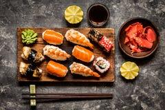 Sushi und Sushirollen, Sushi nigiri auf Steinplatte auf dunklem Hintergrund Lizenzfreie Stockbilder