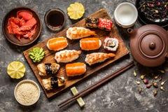 Sushi und Sushirollen, Sushi nigiri auf Steinplatte auf dunklem Hintergrund Stockbild