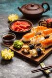Sushi und Sushirollen, Sushi nigiri auf Steinplatte auf dunklem Hintergrund Stockfoto
