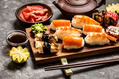Sushi und Sushirollen, Sushi nigiri auf Steinplatte auf dunklem Hintergrund, Senf Wasabi Lizenzfreie Stockfotos