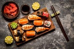 Sushi und Sushirollen, Sushi nigiri auf Steinplatte auf dunklem Hintergrund, Senf Wasabi Stockbild