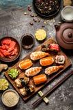 Sushi und Sushirollen, Sushi nigiri auf Steinplatte auf dunklem Hintergrund, Senf Wasabi Lizenzfreie Stockbilder