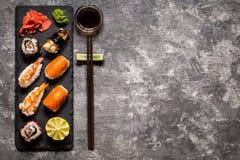 Sushi und Sushirollen, Sushi nigiri auf Steinplatte auf dunklem Hintergrund, Senf Wasabi Stockfotografie