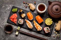 Sushi und Sushirollen, Sushi nigiri auf Steinplatte auf dunklem Hintergrund, Senf Wasabi Stockfotos