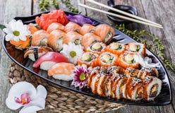 Sushi Vastgestelde die nigiri en sushibroodjes met bloemen op bamboeachtergrond wordt verfraaid Royalty-vrije Stock Foto's