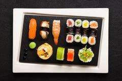 Sushi on white plate on black background Stock Photos