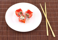 Sushi on white plate and chopsticks over wicker straw mat closeup Stock Images
