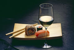 Sushi and wine. Sushi with chopsticks and a glass of wine Stock Photos