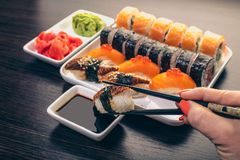 Free Sushi With Eel Dipped In Soy Sauce Royalty Free Stock Image - 145455746