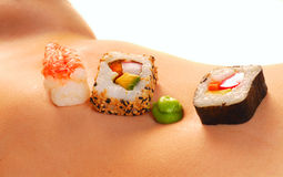 Sushi on a woman's nude stomach. Several pieces of sushi served on a sexy woman's stomach Royalty Free Stock Images
