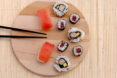 Sushi on wooden board with soy sauce and wasabi. Black chopsticks Stock Images