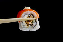 Sushi in wooden chopsticks Royalty Free Stock Photography