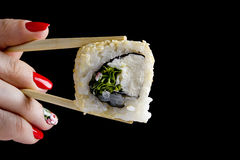Sushi in wooden chopsticks Stock Photo