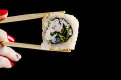 Sushi in wooden chopsticks Stock Images