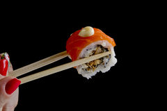 Sushi in wooden chopsticks Royalty Free Stock Photo