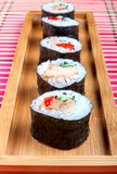 Sushi on a wooden platter and bamboo mat Royalty Free Stock Photos