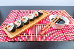 Sushi on a wooden platter and bamboo mat Royalty Free Stock Image