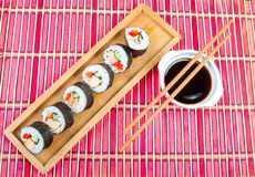 Sushi on a wooden platter and bamboo mat Royalty Free Stock Photo