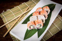 Sushi on wooden table. Sushi maki with salmon and sakura branch over bamboo table Stock Image