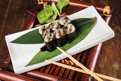 Sushi on wooden table. Sushi maki with salmon and sakura branch over bamboo table Royalty Free Stock Photography