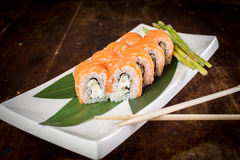 Sushi on wooden table. Sushi maki with salmon and sakura branch over bamboo table Royalty Free Stock Photos
