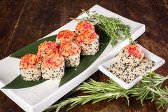 Sushi on wooden table. Sushi maki with salmon and sakura branch over bamboo table Stock Photos
