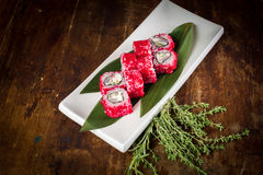 Sushi on wooden table. Sushi maki with salmon and sakura branch over bamboo table Royalty Free Stock Images