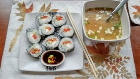 Sushi wrapped in seaweed and filled with smoked salmon, cream cheese and cucumber, with small dipping bowl of soy sauce and wasabi stock photos
