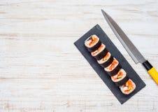 Sushi y cuchillo cortados con el espacio de la copia Fotografía de archivo