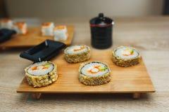 Sushi y maki japoneses de los mariscos en la placa de madera Cierre para arriba imagen de archivo libre de regalías