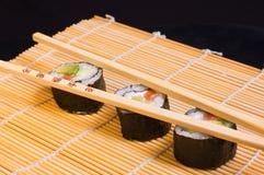 Sushi y palillos de madera Fotos de archivo