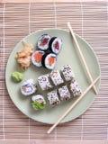 Sushi y palillos en la placa Foto de archivo libre de regalías