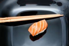 Sushi y palillos en la placa negra Fondo de madera negro Cl Imagen de archivo