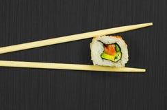 Sushi y palillos en tarjeta de madera negra Fotografía de archivo libre de regalías