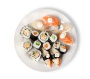 Sushi y rodillos en una placa aislada Imagen de archivo libre de regalías