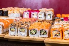 Sushi y rollos clasificados en el tablero de madera en luz oscura Fotos de archivo