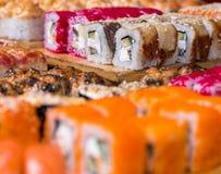 Sushi y rollos clasificados en el tablero de madera en luz oscura Foto de archivo