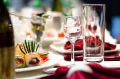 Sushi y vidrios en una mesa de comedor formal Fotografía de archivo