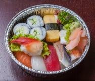 Sushi zu gehen, Nigiri und sortierte Sushirolle im Aluminiumfoliekasten Stockfoto