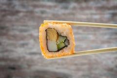 Sushibroodje met eetstokjes over houten achtergrond Royalty-vrije Stock Afbeeldingen