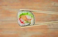 Sushibroodje met eetstokjes over houten achtergrond Royalty-vrije Stock Foto