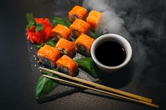 Sushibroodje met roomkaas en gebraden zalm Is verbeterd met eetstokjes van sojasaus, met meer broodjes op zwarte royalty-vrije stock fotografie