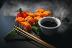 Sushibroodje met roomkaas en gebraden zalm Is verbeterd met eetstokjes van sojasaus, met meer broodjes op zwarte stock afbeeldingen