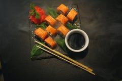 Sushibroodje met roomkaas en gebraden zalm Is verbeterd met eetstokjes van sojasaus, met meer broodjes op zwarte royalty-vrije stock afbeeldingen