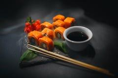 Sushibroodje met roomkaas en gebraden zalm Is verbeterd met eetstokjes van sojasaus, met meer broodjes op zwarte stock foto's