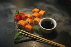 Sushibroodje met roomkaas en gebraden zalm Is verbeterd met eetstokjes van sojasaus, met meer broodjes op zwarte royalty-vrije stock afbeelding