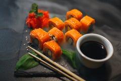 Sushibroodje met roomkaas en gebraden zalm Is verbeterd met eetstokjes van sojasaus, met meer broodjes op zwarte royalty-vrije stock foto's